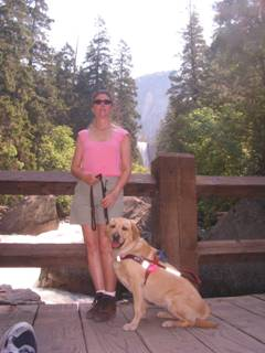 Janice standing with her guide dog , Liza, on a bridge overlooking Vernal Falls at Yosemite National Park.
